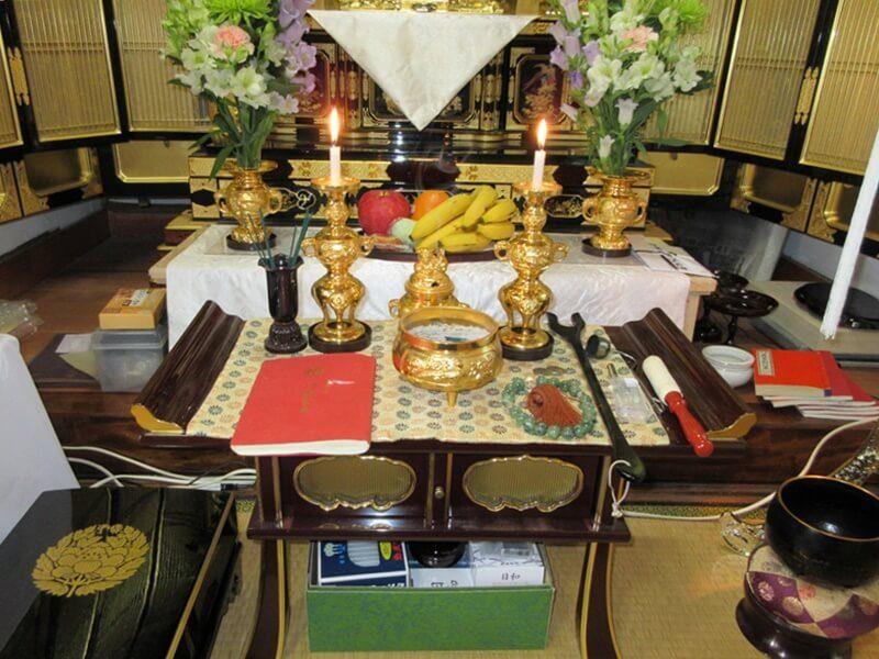 お仏壇前の経机の様子。お経本の他に、香炉や蝋燭が置かれて、ごちゃごちゃしている